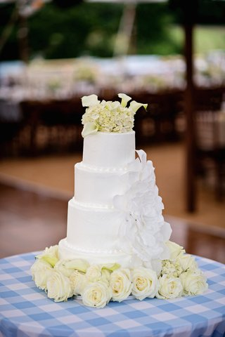 white-wedding-cake-with-large-sugar-flower-topped-with-white-calla-lilies-and-ivory-hydrangeas