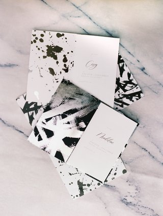 vow-booklets-with-black-paint-splatter-and-silver-brush-strokes-on-vow-booklets