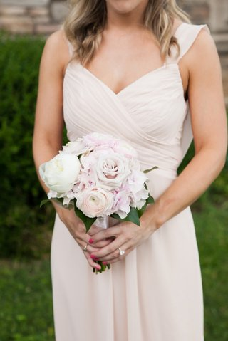 a-bridesmaids-in-a-light-blush-dress-holds-a-bouquets-of-ivory-and-blush-rose-peony-ranunculus