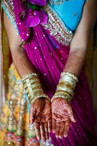 bride-with-henna-on-hands-and-gold-bangles-and-colorful-outfit-blue-purple-yellow