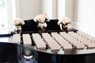 wedding-reception-cocktail-hour-white-escort-card-on-top-of-shiny-black-piano-pink-flowers