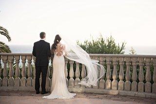 couple-overlooks-oceanside-ceremony-site-flowing-veil-wedding-black-tuxedo-white-dress-pacific