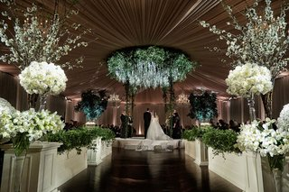 bride-and-groom-on-circle-stage-chuppah-greenery-flower-chandelier-white-rose-hedge-wall-topiary