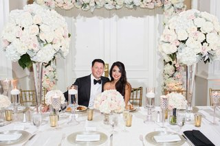 bride-groom-smiling-white-head-table-tall-floral-centerpieces-pink-white-green-vases-floral-arch