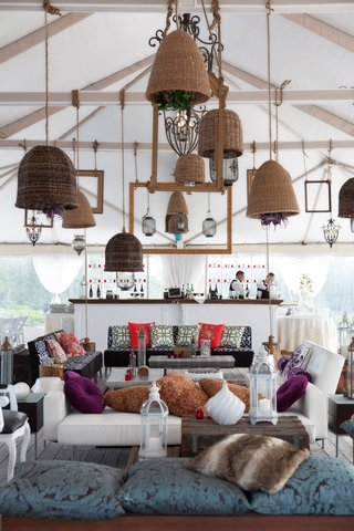 tented-wedding-cocktail-hour-with-wicker-lighting-and-plush-seating