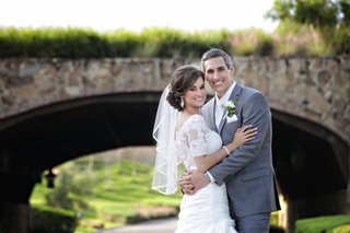woman-in-lace-wedding-dress-and-man-in-grey-suit
