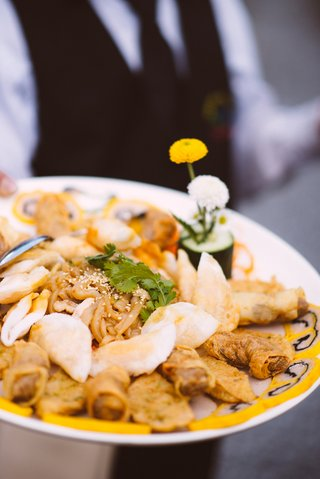 dim-sum-noodles-egg-rolls-and-sesame-seeds-on-plate