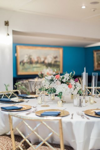 round-wedding-reception-table-gold-chairs-gold-charger-plate-navy-blue-napkin-to-match-walls