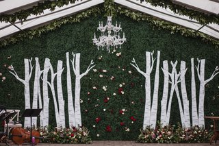 wedding-ceremony-altar-chandelier-greenery-hedge-wall-birch-tree-trunks-flowers-at-base-tent