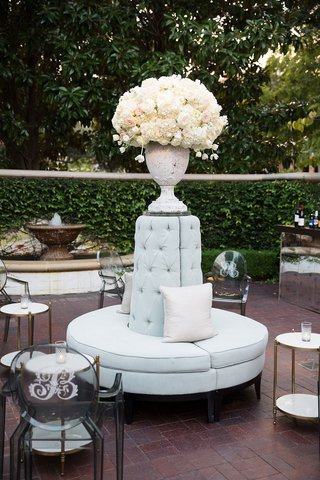 flower-arrangement-on-top-of-round-settee-tufted-pillow-monogram-on-ghost-chairs-side-tables-candles