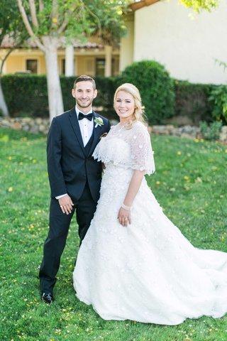 bride-in-oscar-de-la-renta-wedding-dress-with-cape-and-groom-in-tuxedo-and-bow-tie