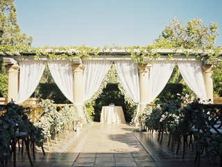 ceremony-altar-with-columns-white-drapery-greenery