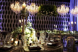 pillar-candle-wrapped-by-fern-in-hurricane-and-brass-candlestick-wedding-centerpiece