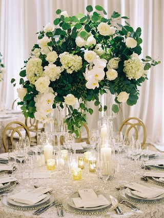 wedding-reception-circular-table-gold-chairs-candles-tall-centerpiece-greenery-white-hydrangea-peony