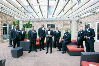 groom-and-groomsmen-in-black-tuxedos-in-outdoor-lounge-area