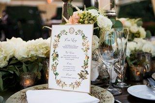 wedding-reception-menu-card-gold-border-monogram-orange-flower-leaf-motif-white-flowers-china
