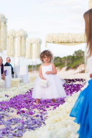 flower-girl-in-white-dress-walks-down-flower-petal-sand-aisle