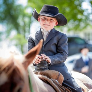 young-ring-bearer-boy-riding-western-saddle-horse