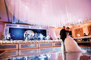 bride-and-groom-first-dance-on-dance-floor-with-crystal-ceiling-treatment-and-pink-lighting