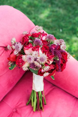 red-pink-purple-flowers-bouquet-floral-arrangement-on-pink-couch-outside-roses-peonies-dahlias