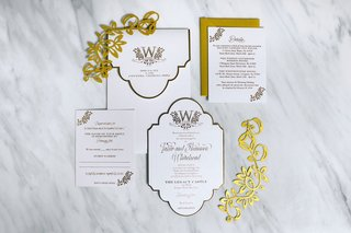 white-gold-wedding-invitation-on-marble-table-gold-laser-cut-details-die-cut-invite-monogram