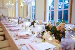 view-of-long-table-with-flower-runner-cut-crystal-candle-votives-pink-napkins-atop-gold-charger