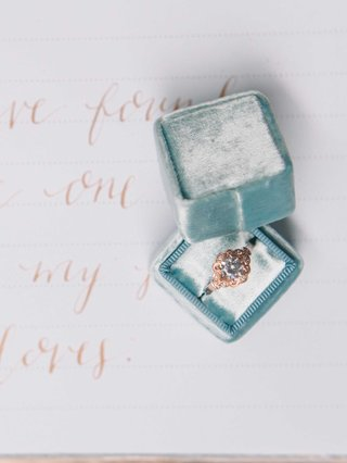 a-rose-gold-ring-inside-a-blue-velvet-the-mrs-box-on-a-white-guest-book-with-rose-gold-calligraphy