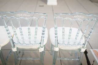 clear-wedding-guest-ceremony-chairs-white-cushions-with-white-calligraphy-names-written-on-back