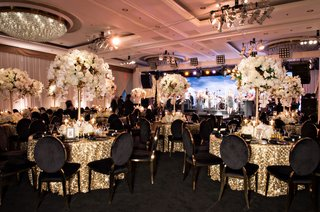 ballroom-anniversary-party-gold-linen-black-gold-chairs-white-flower-arrangements-chandelier-stage