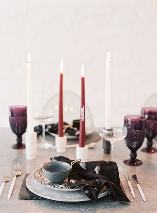 wedding-reception-metal-table-plate-with-black-napkin-white-burgundy-tall-candles-purple-glassware