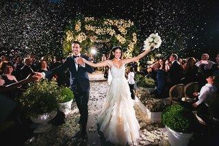 bride-and-groom-recession-wedding-ceremony-outdoor-confetti-in-air-dark-night-ceremony-photo