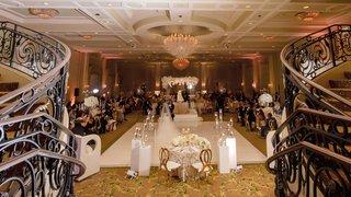 wedding-reception-ballroom-white-dance-floor-flowers-gold-metallic-chairs-chandelier-staircase