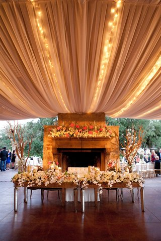 head-table-and-sweetheart-bench-in-front-of-tented-fireplace