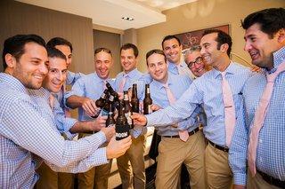 groomsmen-in-gingham-shirts-cheers-beer-botles