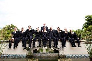 groom-and-groomsmen-sitting-on-mediterranean-bridge