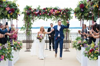 groom-holding-brides-hand-and-pumping-fist-after-ceremony-ending-with-colorful-florals
