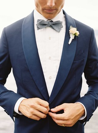 groom-buttoning-up-navy-blue-tuxedo-jacket-with-grey-bow-tie-white-shirt-ivory-flower-boutonniere