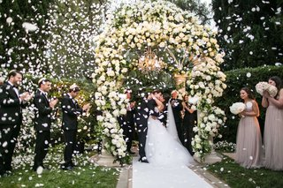 bride-and-groom-kissing-during-wedding-ceremony-with-white-flower-petals-exploding-in-celebration