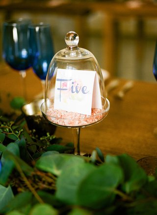 wedding-reception-table-number-tent-in-glass-dome-mini-cake-dome-greenery-wood-table