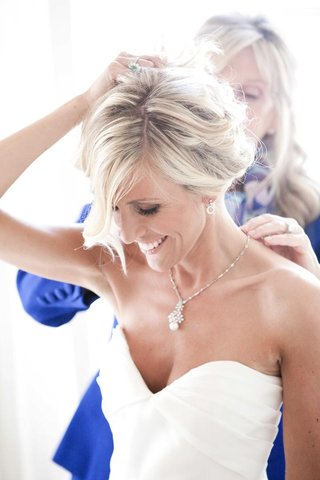 mother-of-bride-puts-necklace-on-blonde-bride