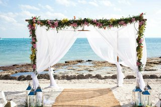 white-fabric-flower-arch-on-beach-for-wedding-ceremony