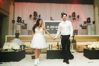 bride-in-short-overskirt-and-bridal-sneakers-with-groom-in-new-years-eve-party-hat-by-countdown
