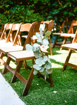 wedding-ceremony-outside-at-lombardi-house-grass-lawn-wood-folding-chair-green-leaves-pink-flowers