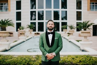 wedding-in-miami-florida-groom-waiting-for-first-look-green-tux-jacket-black-velvet-lapels-pocket