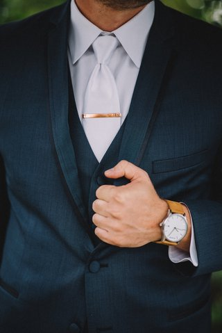 groom-in-navy-blue-suit-with-brown-watch-and-personalized-tie-clip