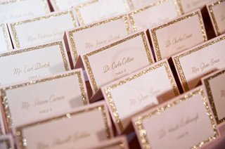 wedding-escort-cards-gold-glitter-board-calligraphy-tables-in-black-ink