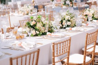 long-kings-table-with-white-linen-low-centerpiece-gold-back-chairs-peach-accent-color-candle-votive