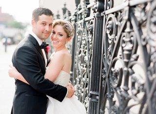 groom-hugs-bride-in-strapless-reem-acra-wedding-dress