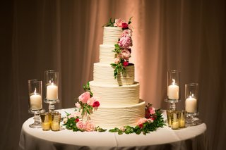 wedding-cake-with-five-ivory-layer-tier-with-candles-pink-flowers-green-leaves-greenery