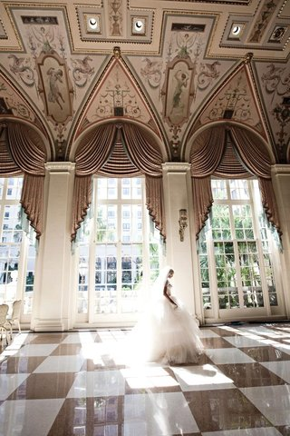 bride-walking-through-mediterranean-ballroom-at-the-breakers